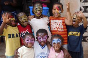 Glückliche kleine Fußballer feiern und spielen gemeinsam