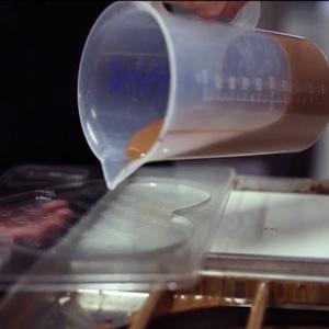 Vollmilchschokolade wird in die Herzform gegossen