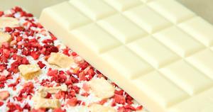 Weiße Schokolade mit roten und beigen Früchtstückchen bestreut © chocri